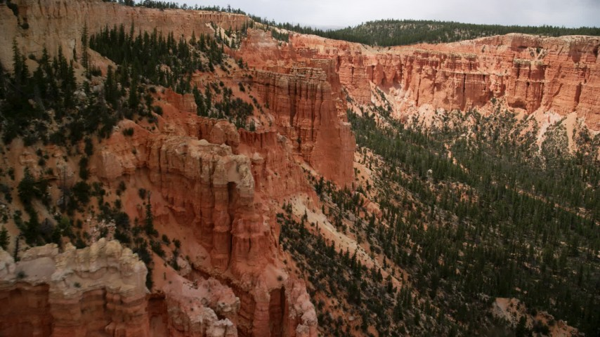6K stock footage aerial video of flying by hoodoos overlooking box canyon between mesas, Bryce Canyon National Park, Utah Aerial Stock Footage | AX130_467