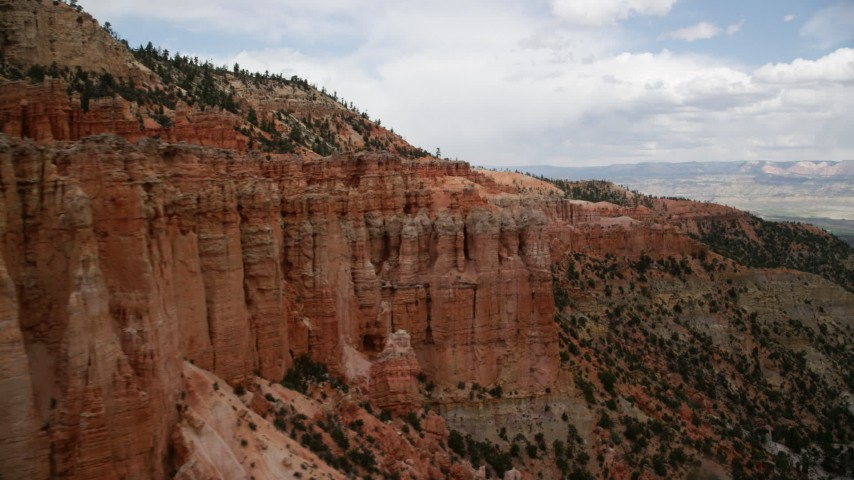 Flying by groups of hoodoos, mesa cliffside, Bryce Canyon National Park, Utah Aerial Stock Footage | AX130_470