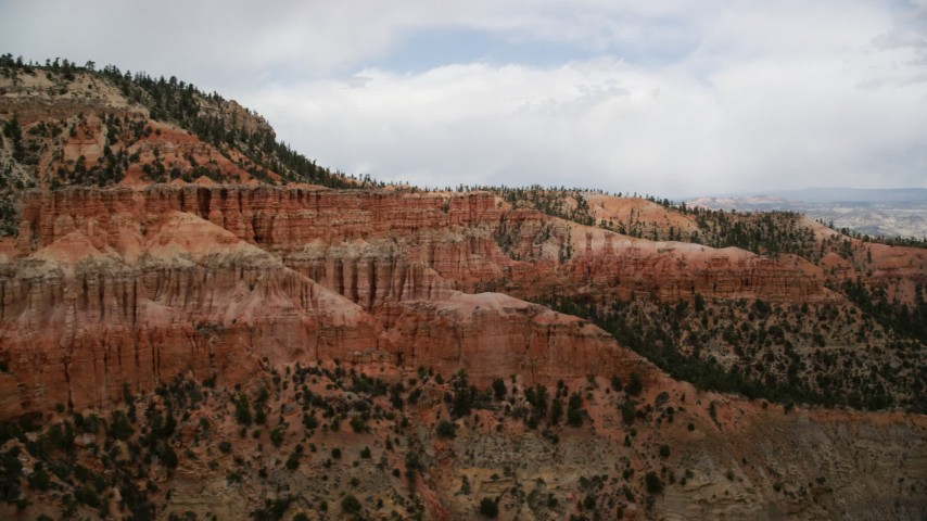Flying by hoodoos on the side of mesas, Bryce Canyon National Park, Utah Aerial Stock Footage | AX130_471