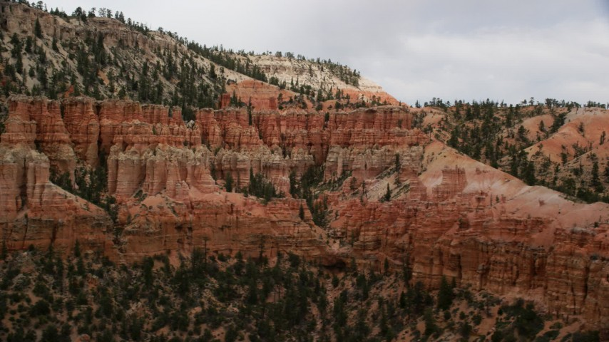 Flying by group of hoodoos beside a mesa, Bryce Canyon National Park, Utah Aerial Stock Footage | AX130_472
