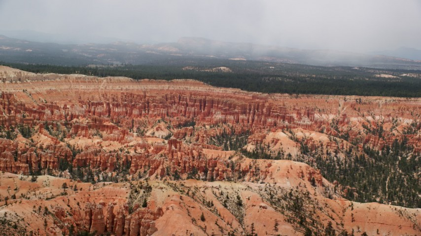Flying over a mesa, tilt down to hoodoos, buttes, Bryce Canyon National Park, Utah Aerial Stock Footage | AX130_473