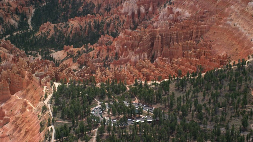 Flying away from hoodoos, buttes, seen from over parking area, Bryce Canyon National Park, Utah Aerial Stock Footage | AX130_489