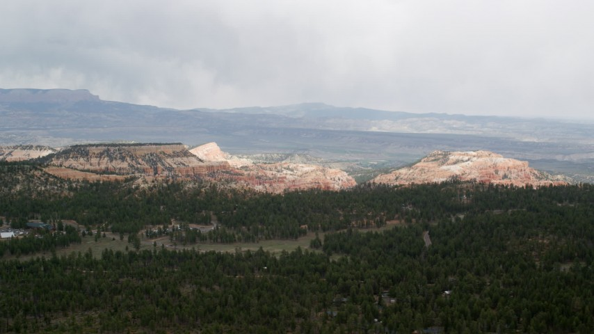 Flying by green forest, mesas in the background, Bryce Canyon National Park, Utah Aerial Stock Footage | AX131_006