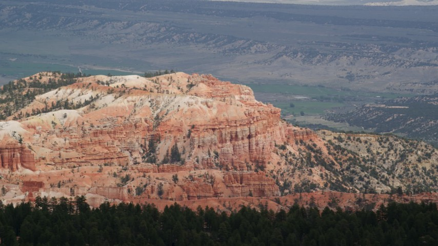 Flying by cliffside hoodoos, buttes, distant valley, Bryce Canyon National Park, Utah Aerial Stock Footage | AX131_007