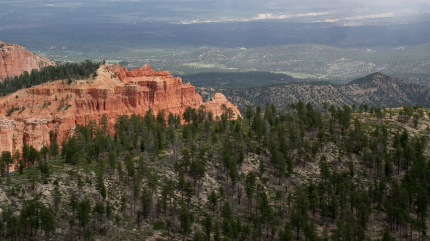 6K stock footage aerial video of flying by top of butte, forest, distant valley, Bryce Canyon National Park, Utah Aerial Stock Footage | AX131_011