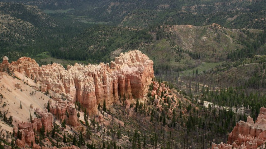 Flying by butte, surrounded by trees, Bryce Canyon National Park, Utah Aerial Stock Footage | AX131_012