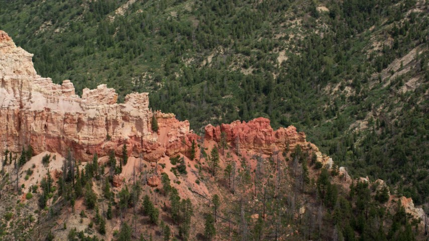 Flying by jagged butte, revealing forested valley, Bryce Canyon National Park, Utah Aerial Stock Footage | AX131_016