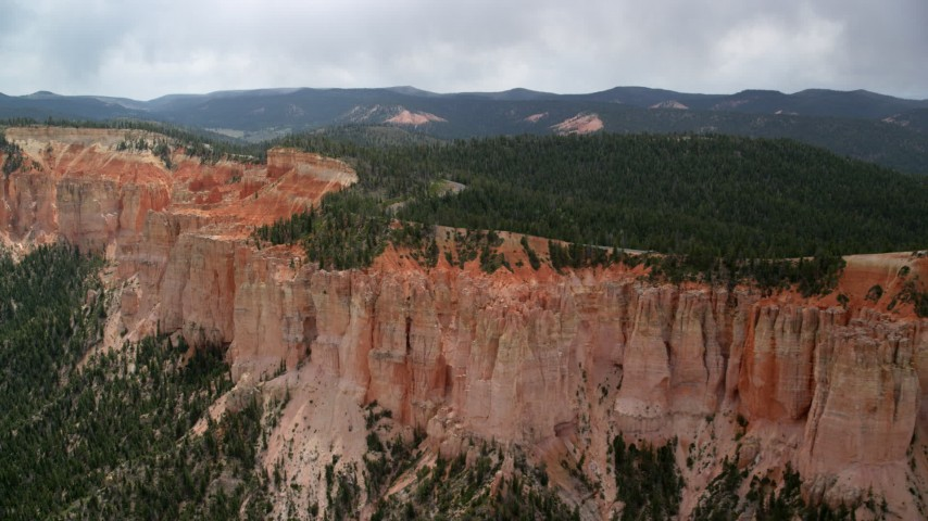 6K stock footage aerial video of passing by rock formations, Pink Cliffs, trees, Bryce Canyon National Park, Utah Aerial Stock Footage | AX131_022