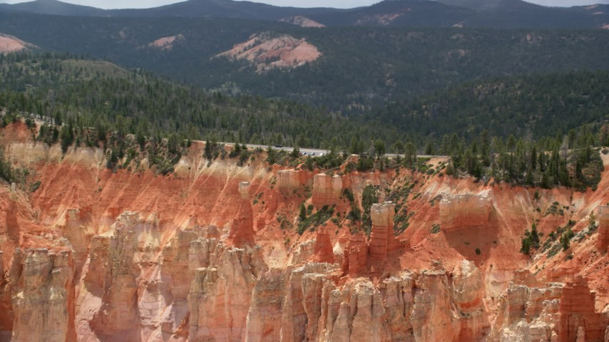 Flying by Pink Cliffs, hoodoos, topped with trees, Bryce Canyon National Park, Utah Aerial Stock Footage | AX131_024