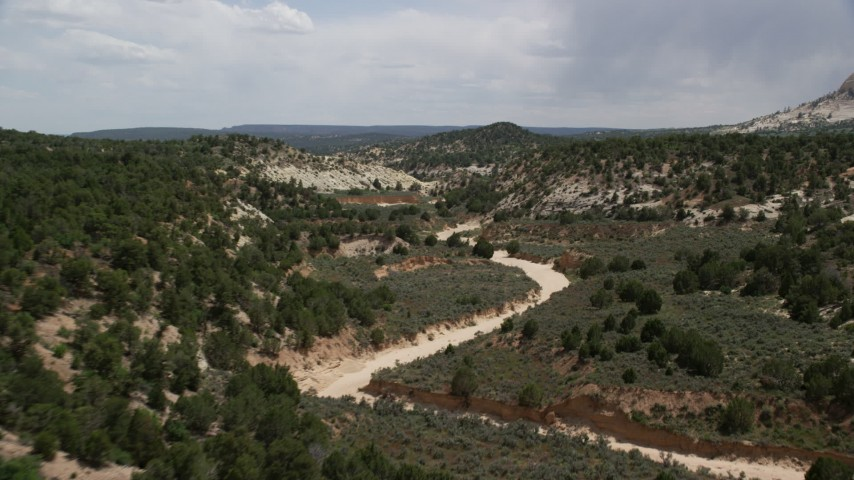 Flying low over dry riverbed, Grand Staircase-Escalante National Monument, Utah Aerial Stock Footage | AX131_058