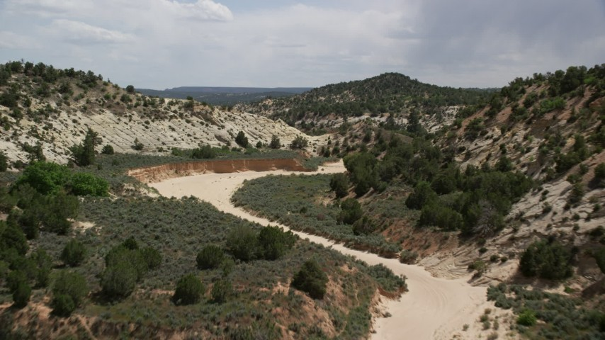 Flying low over dry riverbed, Grand Staircase-Escalante National Monument, Utah Aerial Stock Footage | AX131_059