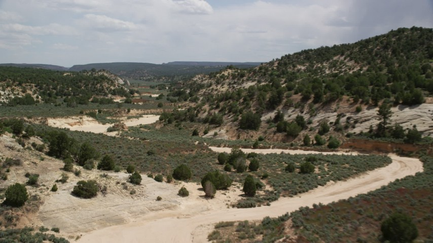 Flying low over dry riverbed, Grand Staircase-Escalante National Monument, Utah Aerial Stock Footage | AX131_060