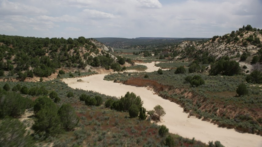 Flying low over a dry riverbed, Grand Staircase-Escalante National Monument, Utah Aerial Stock Footage | AX131_061