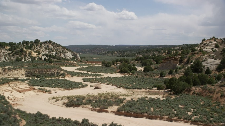 6K stock footage aerial video of following a dry riverbed past hills, Grand Staircase-Escalante National Monument, Utah Aerial Stock Footage | AX131_062