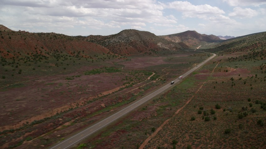 6K stock footage aerial video of following a big rig and bus on Highway 89, Glen Canyon National Recreation Area, Utah, Arizona Aerial Stock Footage | AX131_087
