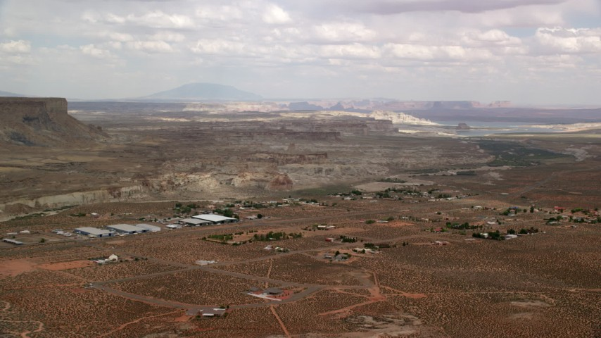 6K stock footage aerial video of a tiny desert town, mesa in the distance, Big Water, Utah Aerial Stock Footage | AX131_119