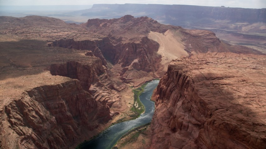 6K stock footage aerial video of flying over Colorado River, bordered by rugged cliffs, Glen Canyon, Arizona Aerial Stock Footage | AX131_187