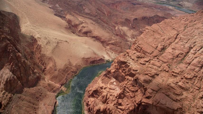 Bird's eye view rounding a cliff, following Colorado River, Glen Canyon, Arizona Aerial Stock Footage | AX131_190