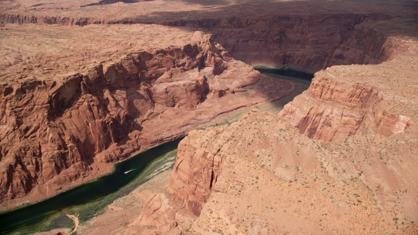 6K stock footage aerial video of approaching Colorado River as a boat speeds by, Glen Canyon, Arizona Aerial Stock Footage | AX131_198