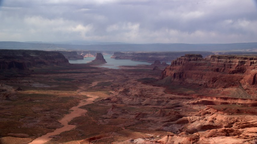 Flying by buttes, Lake Powell in the distance, Navajo Nation Reservation, Arizona Aerial Stock Footage | AX132_008