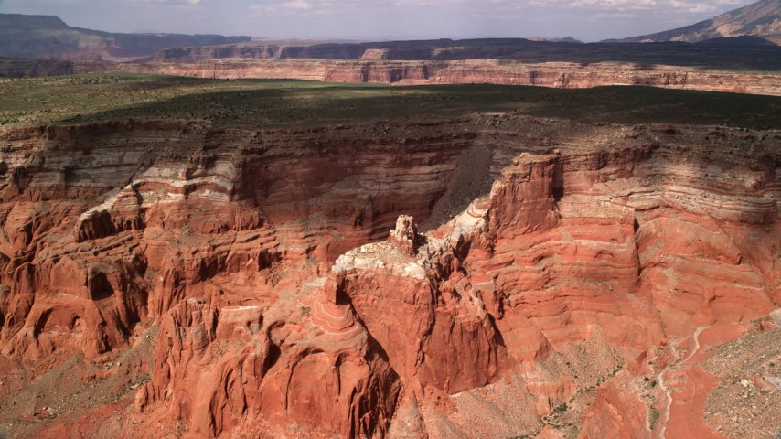 Approaching canyon, mesa, butte, Navajo Nation Reservation, Utah Aerial Stock Footage | AX132_014