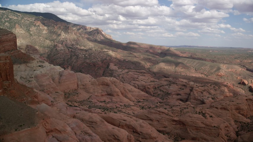 Flying by rock formations, mountain slopes, Navajo Mountain, Utah Aerial Stock Footage AX132_067