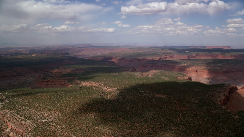 Flying by desert canyons, mesas, Navajo Nation Reservation, Arizona, Utah Aerial Stock Footage | AX132_079