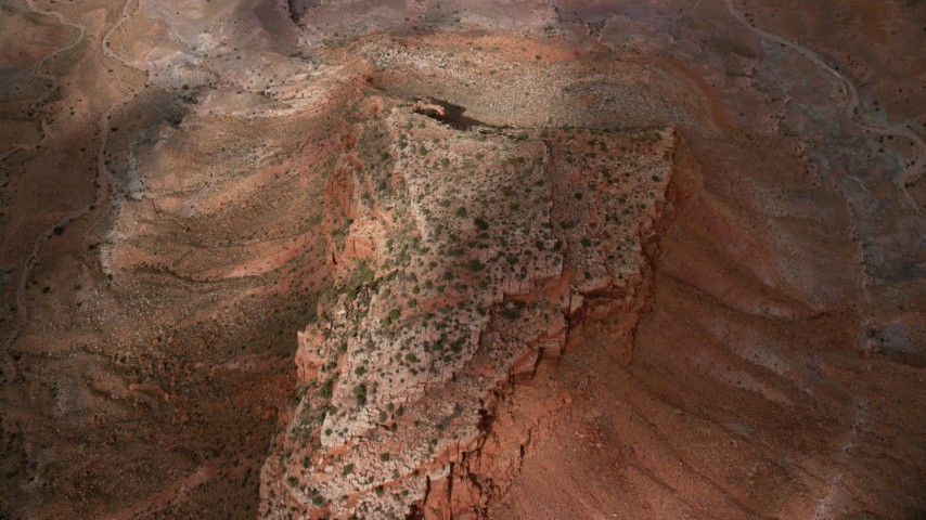 Bird's eye view flying over a small mesa, Navajo Nation Reservation, Arizona, Utah Aerial Stock Footage | AX132_082