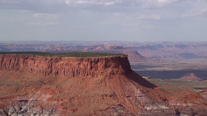 Flying by a tall desert mesa, Navajo Nation Reservation, Arizona, Utah Aerial Stock Footage | AX132_092