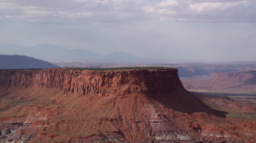 Flying by a tall desert mesa, Navajo Nation Reservation, Arizona, Utah Aerial Stock Footage | AX132_093