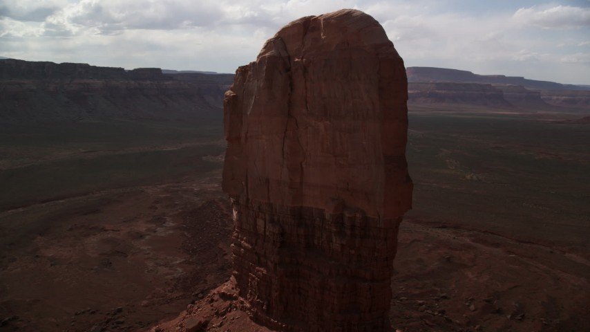 Orbiting tall butte surrounded by mesas, Navajo Nation Reservation, Arizona, Utah Aerial Stock Footage | AX132_106