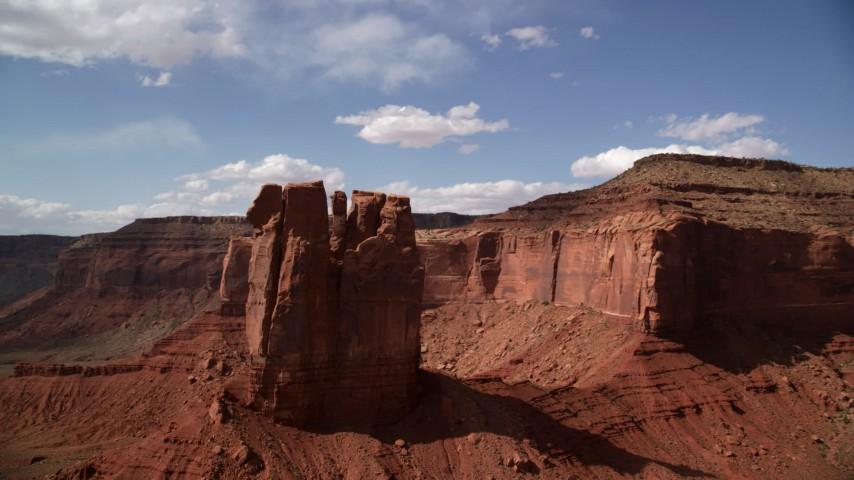 Orbiting tall desert butte near mesas, Navajo Nation Reservation, Arizona, Utah Aerial Stock Footage | AX132_114