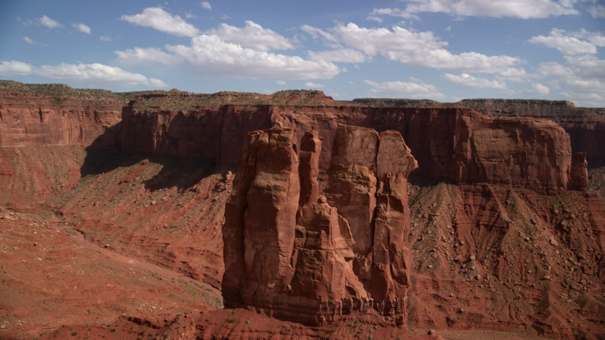 Flying away from tall desert butte, mesas, Navajo Nation Reservation, Arizona, Utah Aerial Stock Footage | AX132_117