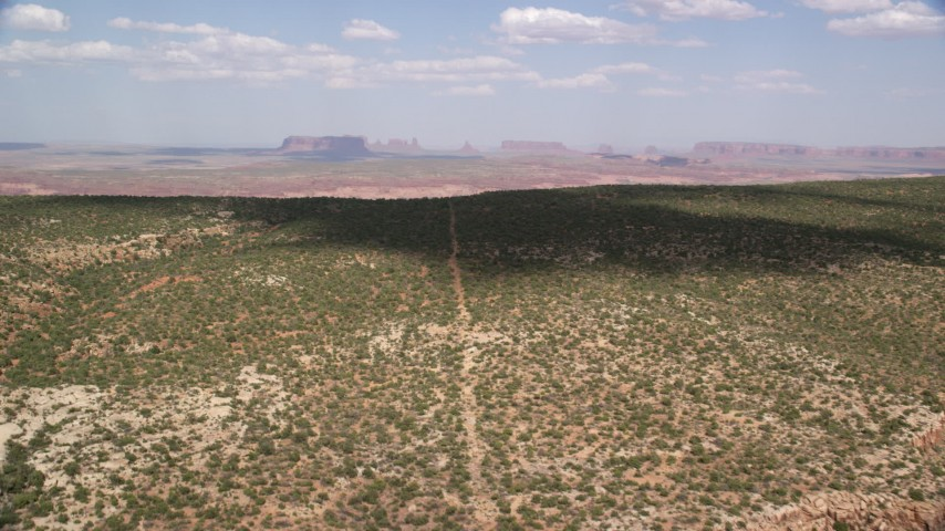 6K stock footage aerial video approaching Monument Valley from mesa in Navajo Nation Reservation, Arizona, Utah Aerial Stock Footage | AX132_120
