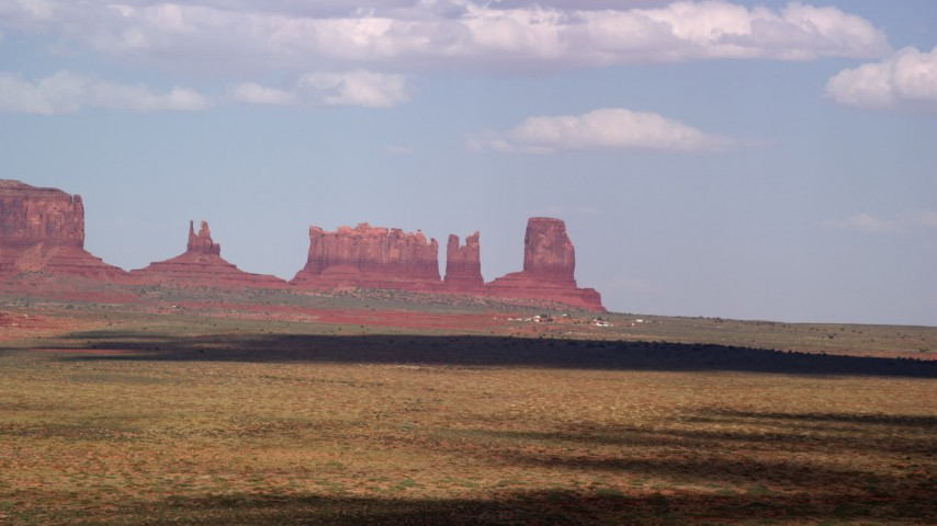 Flying by four desert buttes; Monument Valley, Arizona, Utah Aerial Stock Footage | AX132_133