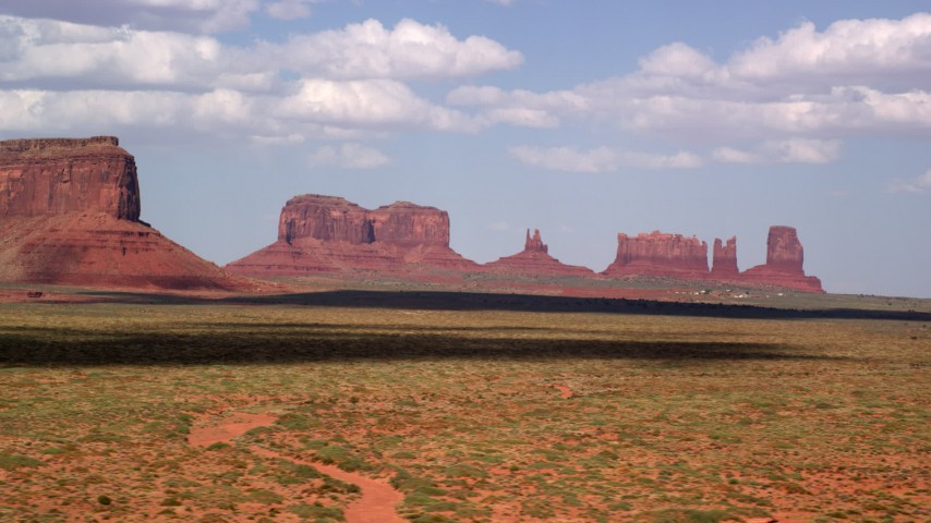 Flying by four desert buttes, Monument Valley, Arizona, Utah Aerial Stock Footage | AX132_135