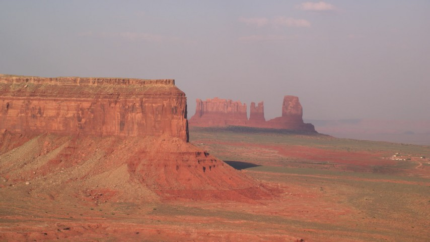 Flying by Eagle Mesa, buttes, Monument Valley, Utah, Arizona, sunset Aerial Stock Footage | AX133_003