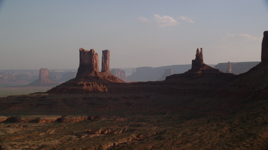 Flying by buttes, desert valley, Monument Valley, Utah, Arizona, sunset Aerial Stock Footage | AX133_014