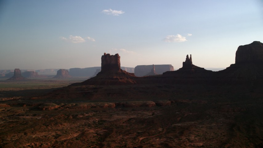 Flying by buttes, desert valley, Monument Valley, Utah, Arizona, sunset Aerial Stock Footage | AX133_015