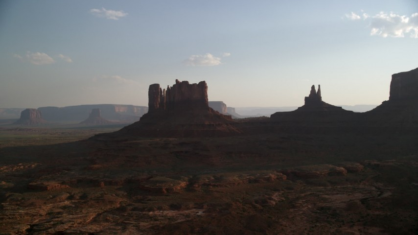 Flying by buttes, desert valley, Monument Valley, Utah, Arizona, sunset Aerial Stock Footage | AX133_016