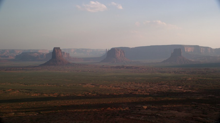 Fly by buttes, mesas across desert valley, Monument Valley, Utah, Arizona, sunset Aerial Stock Footage | AX133_017