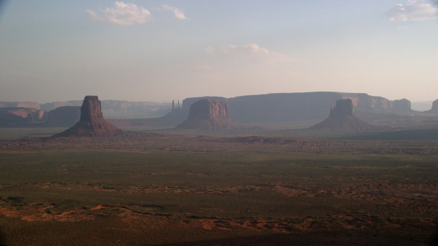 Fly by buttes, mesas across desert valley, Monument Valley, Utah, Arizona, twilight Aerial Stock Footage | AX133_018