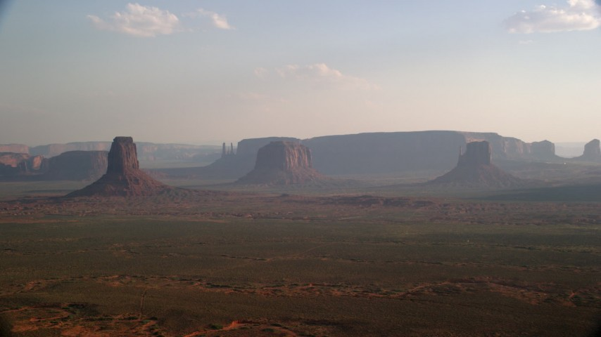 Fly by buttes, mesas across desert valley, Monument Valley, Utah, Arizona, twilight Aerial Stock Footage | AX133_019