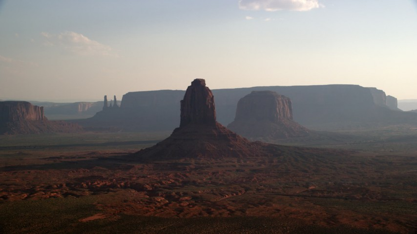 Flying by buttes, mesa in a desert valley, Monument Valley, Utah, Arizona, twilight Aerial Stock Footage | AX133_024