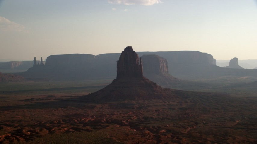 Flying by buttes, mesas, desert valley, Monument Valley, Utah, Arizona, twilight Aerial Stock Footage | AX133_025