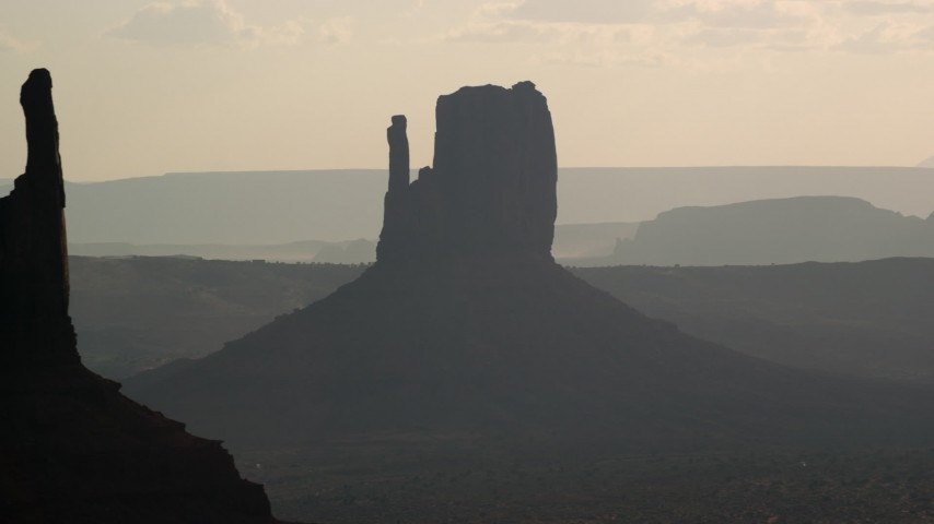 Flying by West Mitten Butte, Monument Valley, Utah, Arizona, twilight Aerial Stock Footage | AX133_027