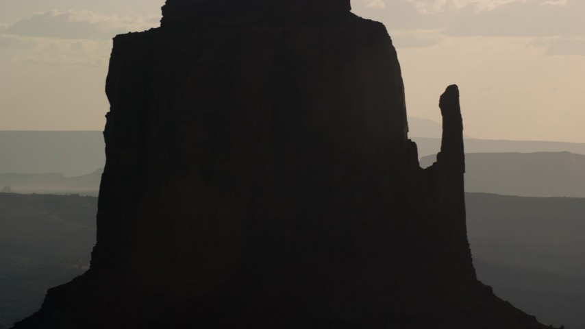 Flying by East Mitten Butte, Monument Valley, Utah, Arizona, twilight Aerial Stock Footage | AX133_028