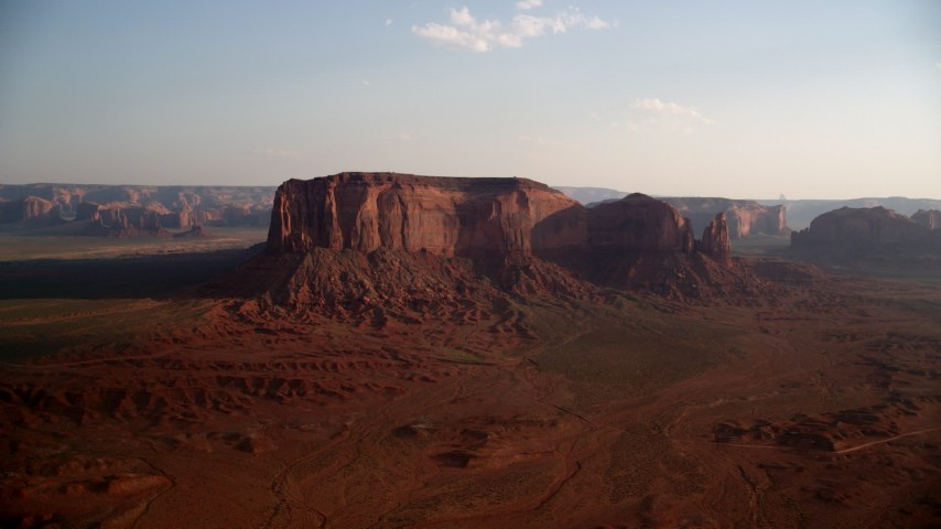 Flying by Spearhead Mesa, Monument Valley, Utah, Arizona, sunset Aerial Stock Footage AX133_030