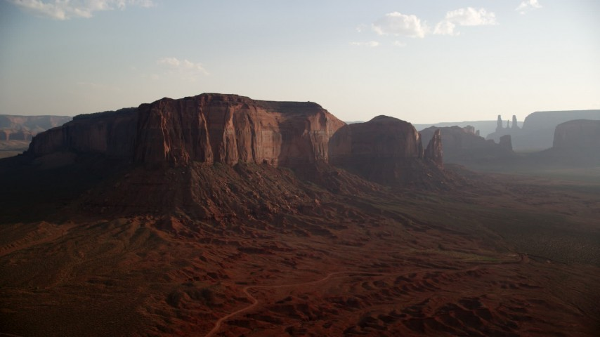Flying by Spearhead Mesa, desert valley, Monument Valley, Utah, Arizona, twilight Aerial Stock Footage | AX133_032