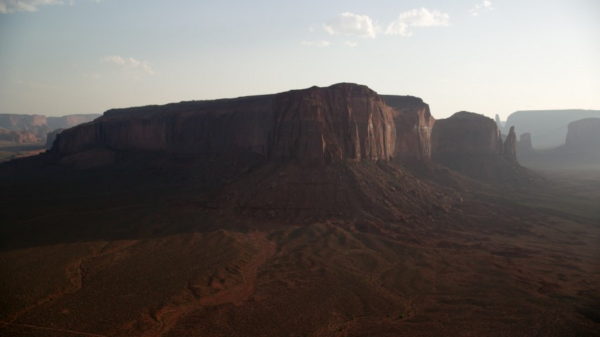 Flying by Spearhead Mesa. desert valley, Monument Valley, Utah, Arizona, twilight Aerial Stock Footage | AX133_033